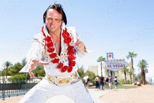 Poster Elvis impersonator dancing by Las Vegas sign