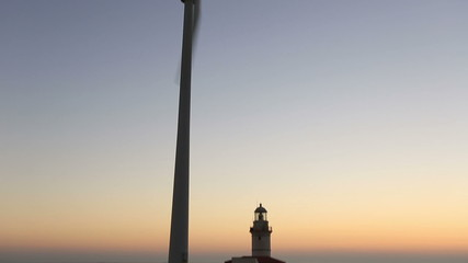 wind turbines generating clean power with lighthouse at sunset
