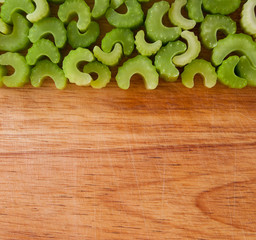 Row of chopped celery pieces against wood