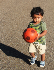 Young boy playing red ball road garden park