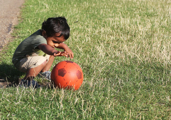 A Young boy reaching red ball green grass garden park