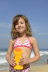 Child at beach holding sunscreen