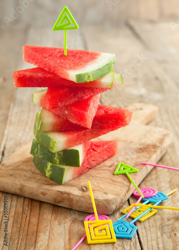 Slices of watermelon on wooden chopping board