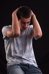 Upset teenager with head in hands wincing from stress, anguish o