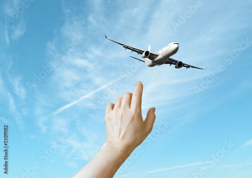 Hand pointing at airplane.