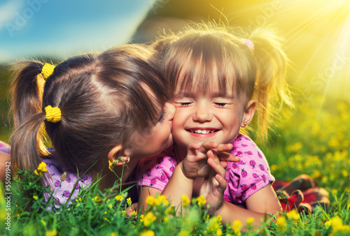 happy girls twin sisters kissing and laughing in the summer outd