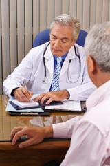 Arzt im Gespräch mit Patient macht Notizen