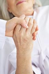 Arzt hält Hand einer Seniorin im Krankenhaus