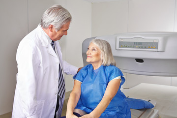 Arzt redet mit Seniorin vor Knochendichtemessung
