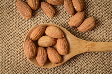 Almonds on a Spoon with Brown Background