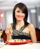 Beautiful woman eating at the restaurant