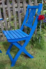 Blauer Gartenstuhl mit roter Rose