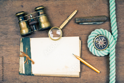 Vintage notebook, compass, binoculars, knife, pencil, magnifying