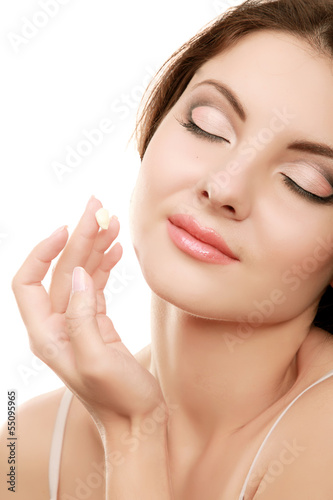 Young woman putting cream on her face