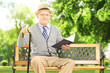 Senior man sitting on a wooden bench and reading a book, in park