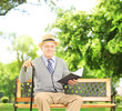 Senior man sitting on a wooden bench and reading a book