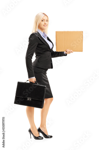 Full length portrait of a blond woman in suit holding a card