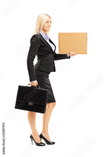 Full length portrait of a young woman in suit holding a card