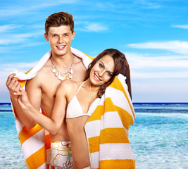 Couple with towel at beach.