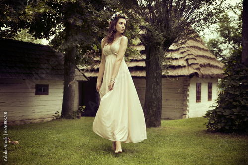 Lady in white dress dancing on the grass