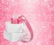 White boxes with gifts with pink ribbons on the beautiful abstra
