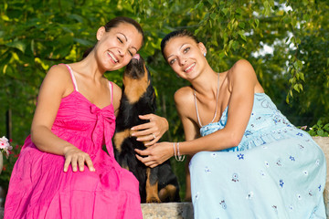two beautiful young woman playing with puppy in park