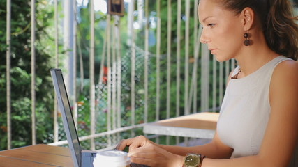 Beautiful young business woman sitting in a cafe with a laptop