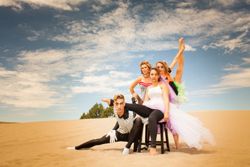 Circus performers victory pose in desert