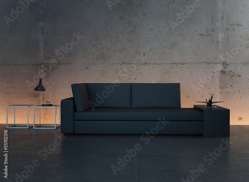 Black couch standing against concrete wall
