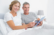 Happy couple using their tablet pc to buy online