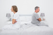 Couple sitting on different sides of bed not talking after dispu