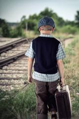 Junge mit Koffer am Bahnhof