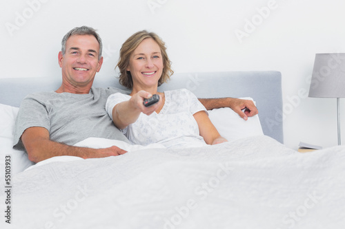 Relaxed couple watching tv in bed looking at camera