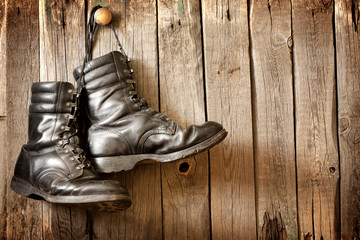 Old military shoes on vintage wooden boards abstract background