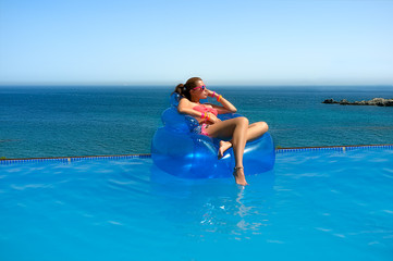 Fashionable Girl Relaxing in the Pool. Summer Vacation