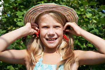 Little girl holding red currants near her ears