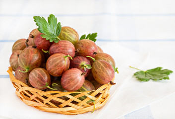 Fresh gooseberries in basket over light background