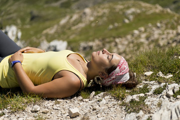 Girl relaxing in a meadow after hiking