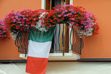 flowering balcony with Geraniums and the Italian flag