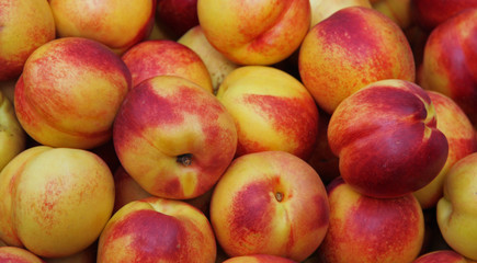 beautiful yellow ripe peaches for sale at vegetable market
