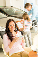 Woman drinking coffee in car retail store