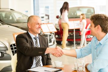 Customer and car salesman shaking hands