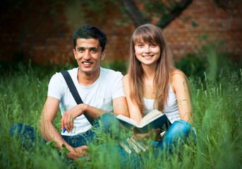 Two students guy and girl studying in park on grass with book