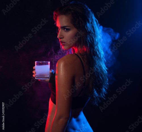 Young hot woman posing and holding a glass of alcohol drink