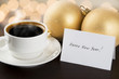 Cup of coffee with New Year decorations and greeting card