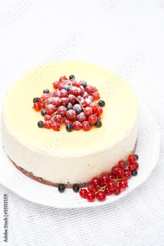 cheesecake decorated with red and black currants, vertical