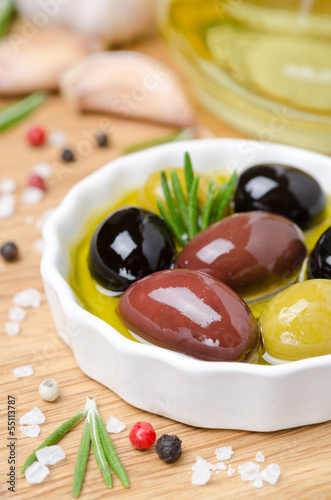 close-up of a bowl with olives in olive oil and spices on a wood