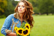 Young fashion woman with a bouquet of sunflowers in the field