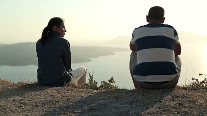 Relationship difficulties, couple sitting on cliff