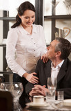 Mature couple in restaurant. Cheerful middle-aged couple looking